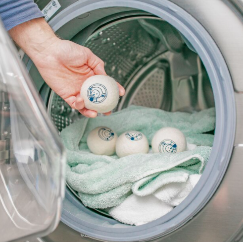 A person throwing a woolen dryer ball into a dryer full of towels