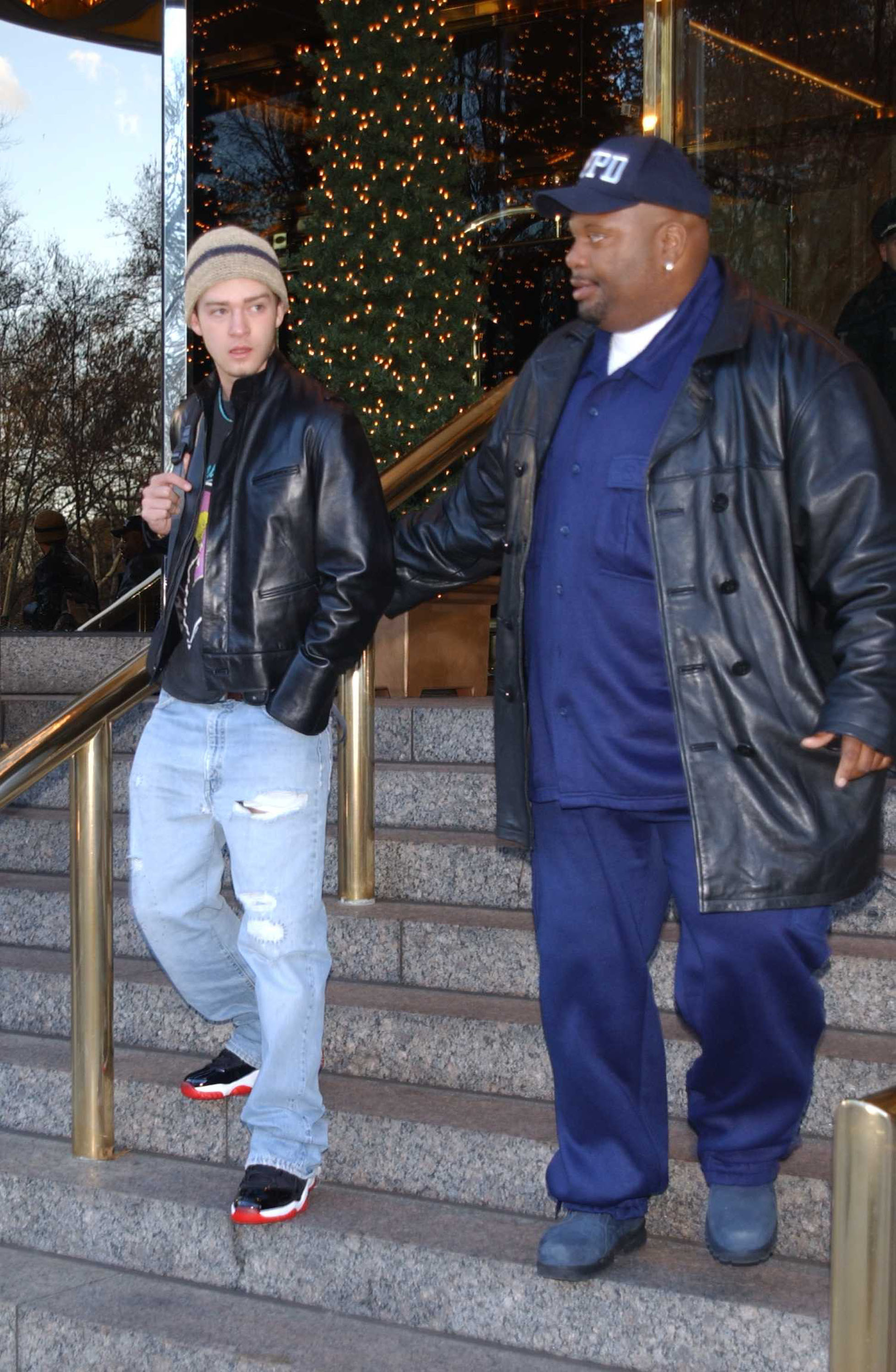 Justin walking out of a building wearing a beanie, leather jacket, and jeans