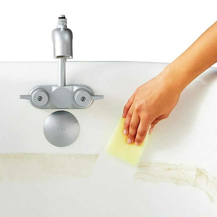 A hand using a Scotch-Brite Dobie Cleaning Pad to clear grime from a bathtub