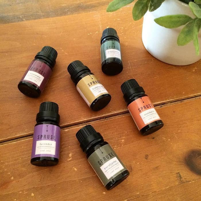 Six essential oils on a wooden countertop