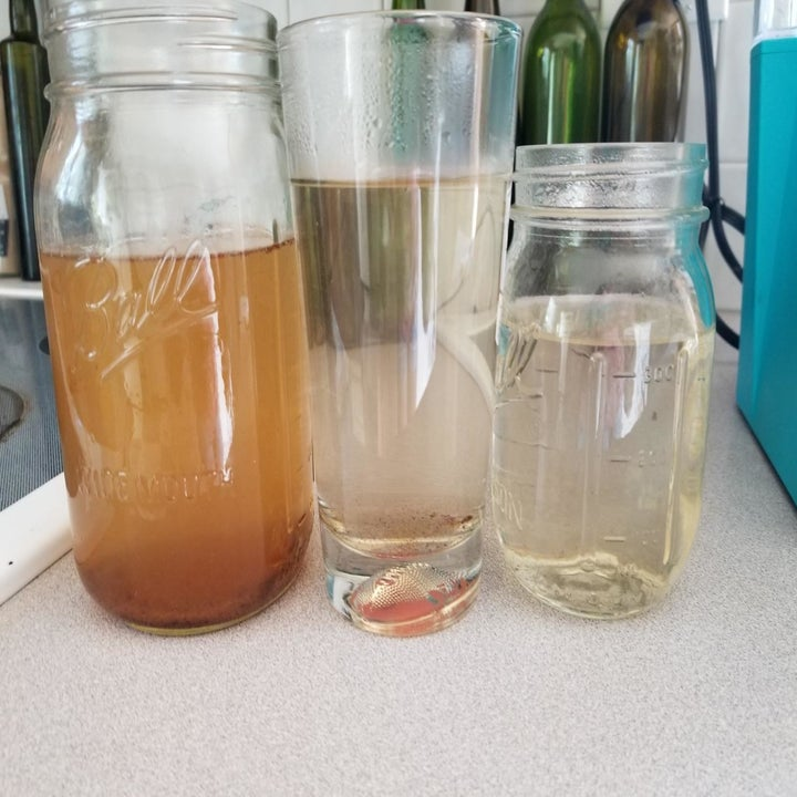 A glass on the left filled with brown water, a glass in the middle filled with cloudy water, and a glass on the right filled with clean water