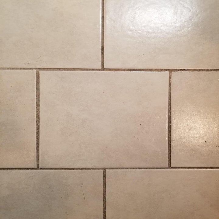 A reviewer photo of a tile floor with dark brown staining on the grout