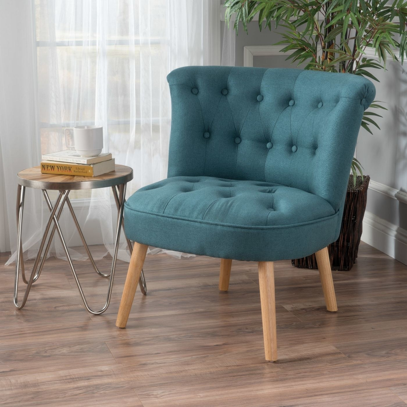 blue tufted accent chair in the corner of a room