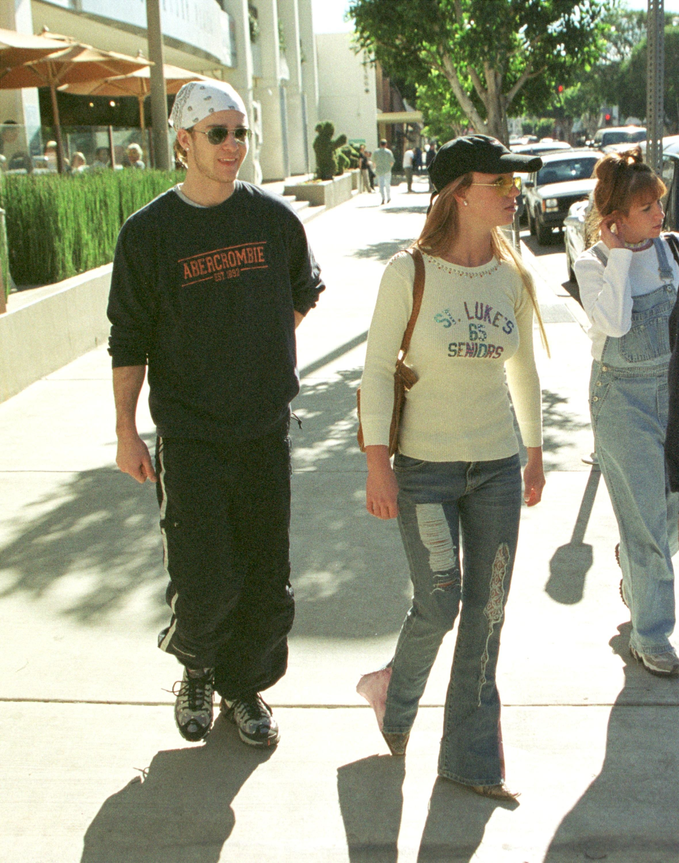 Throwback photo of Justin, wearing a bandana, Abercrombie sweatshirt and track pants, as he walks with Britney, who's wearing a baseball cap and ripped jeans