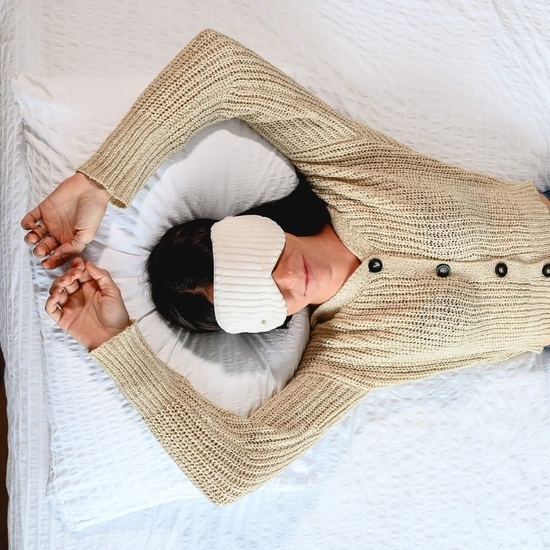 A top-down view of a person laying on a bed while wearing the weighted eye mask