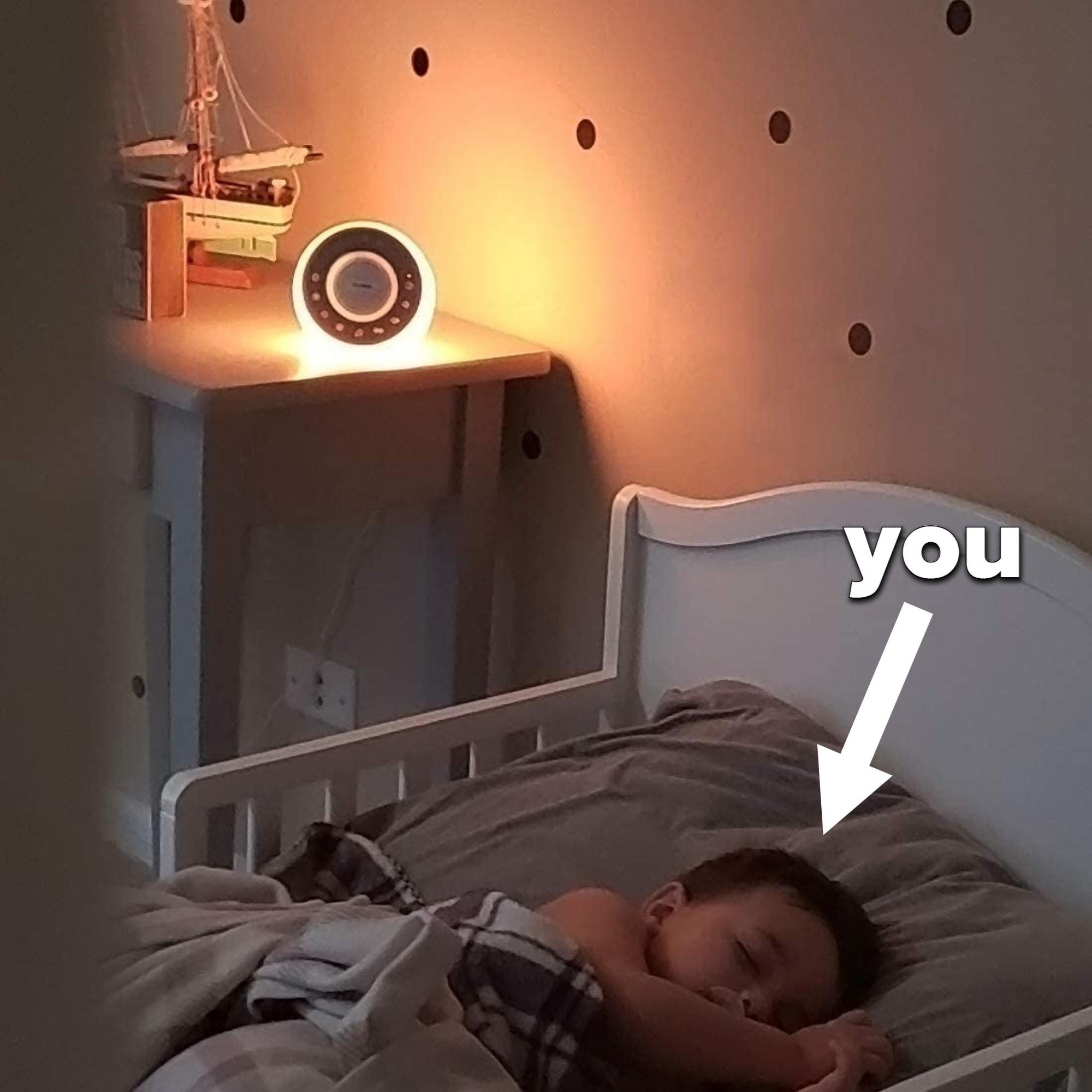 A toddler sleeping beside the white noise night light
