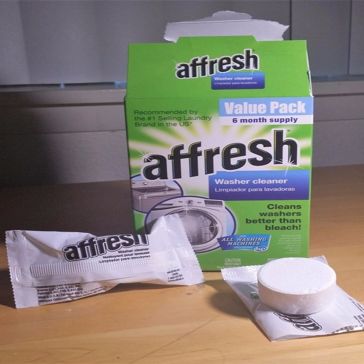 The Affresh Washing Machine Cleaner Tablets packaging next to an open tablet