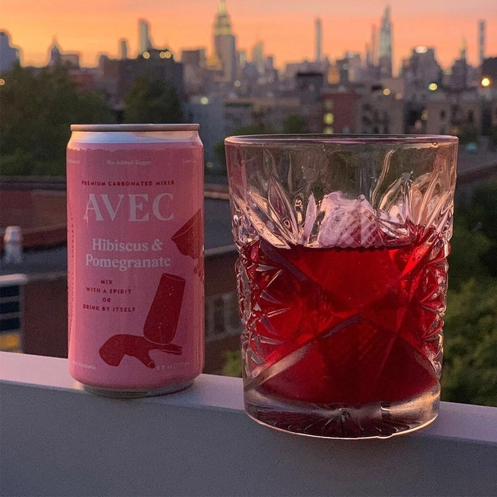 A can and cup with ice and juice on ledge