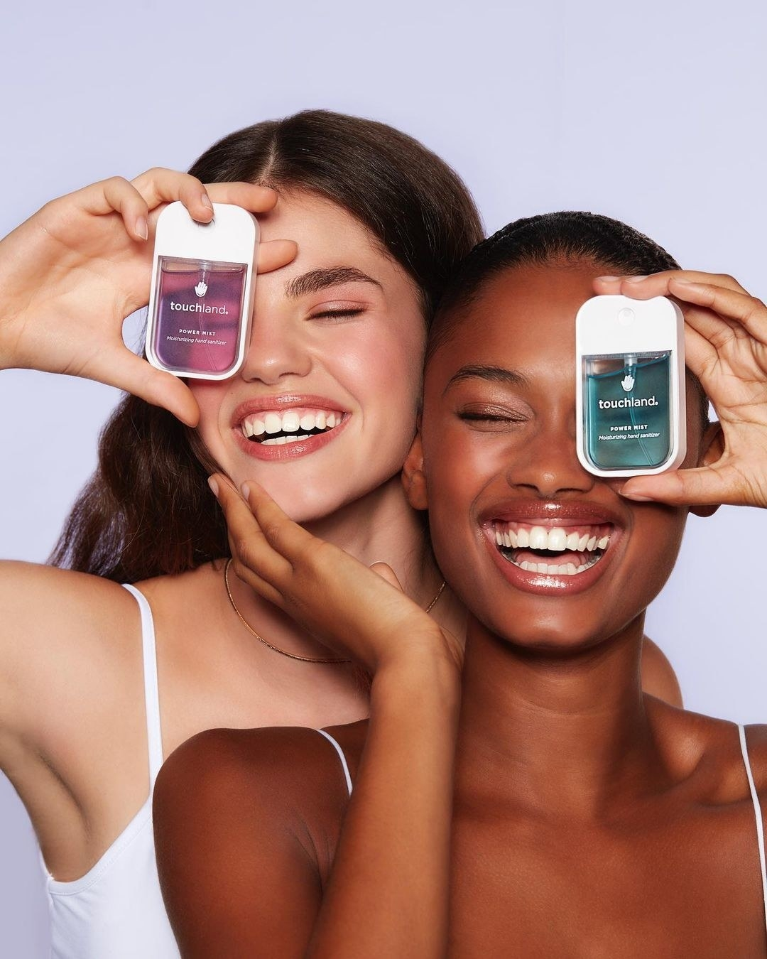 A pair of smiling models holding up bottles of the hand sanitizer
