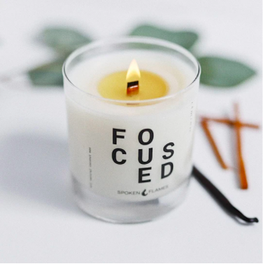 """white candle with """"FOCUSED"""" written on the label"""
