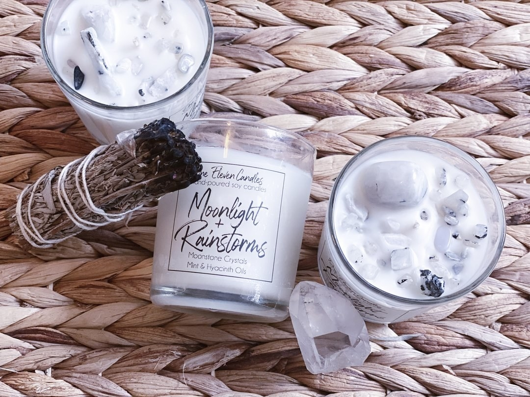 stick of sage with three of the candles with light gray moonstones embedded in the wax