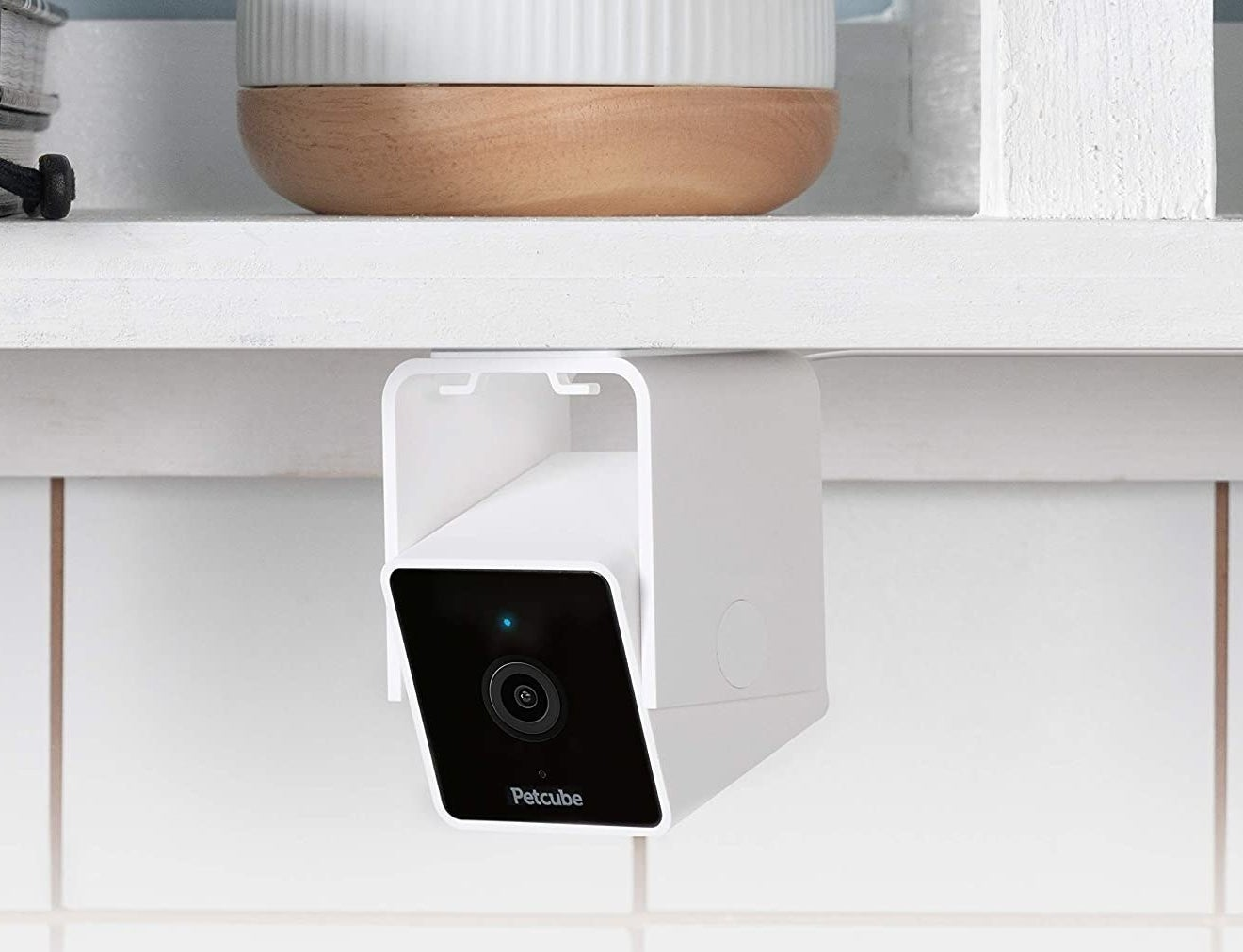 A small camera mounted to the bottom of a kitchen shelf