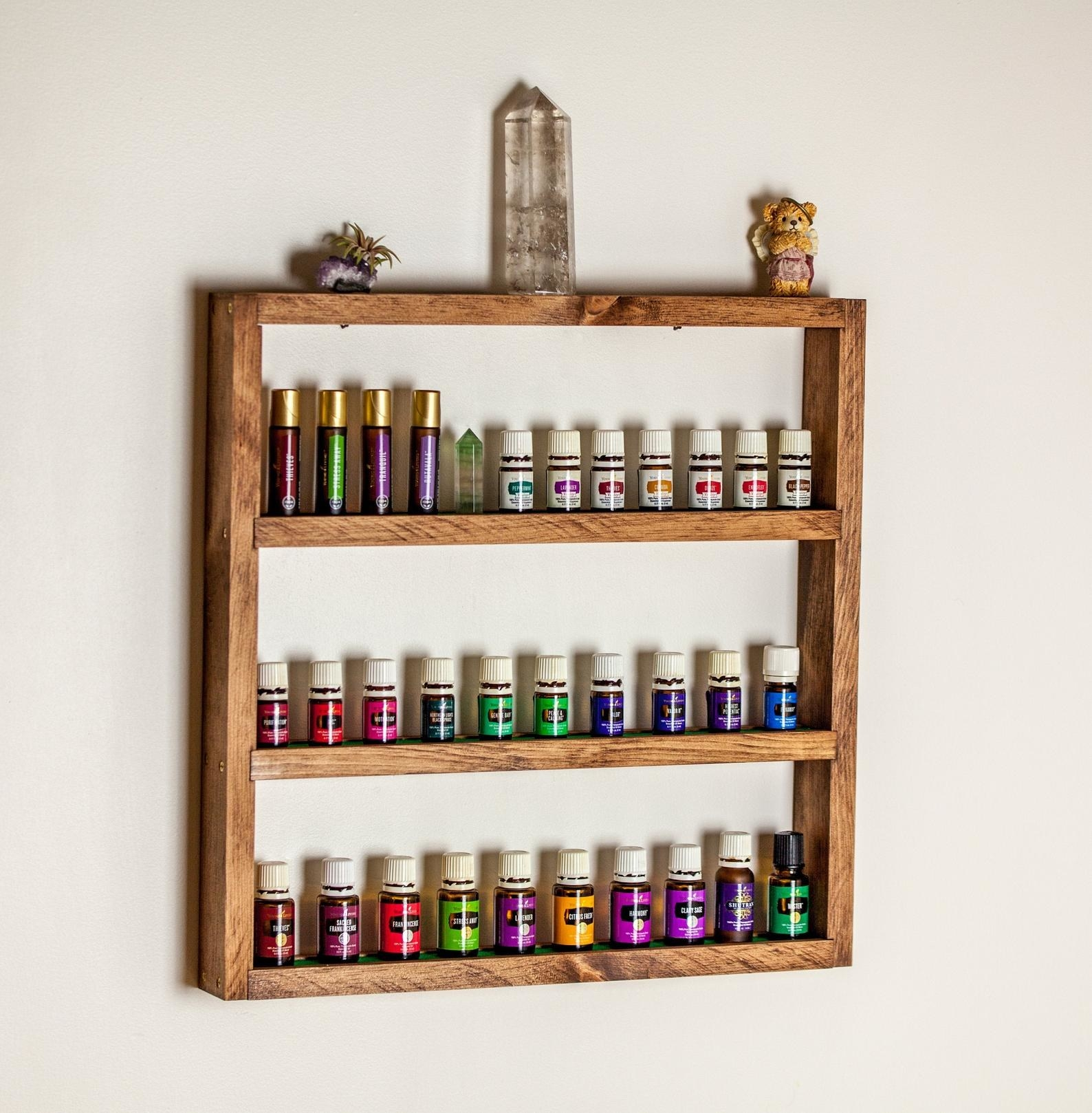 The three-tier shelf holding various bottles of essential oil