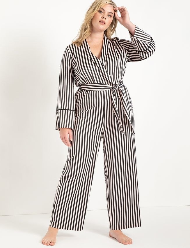 a plus size model wearing the budoir stripe piping trimmed lounge jumpsuit