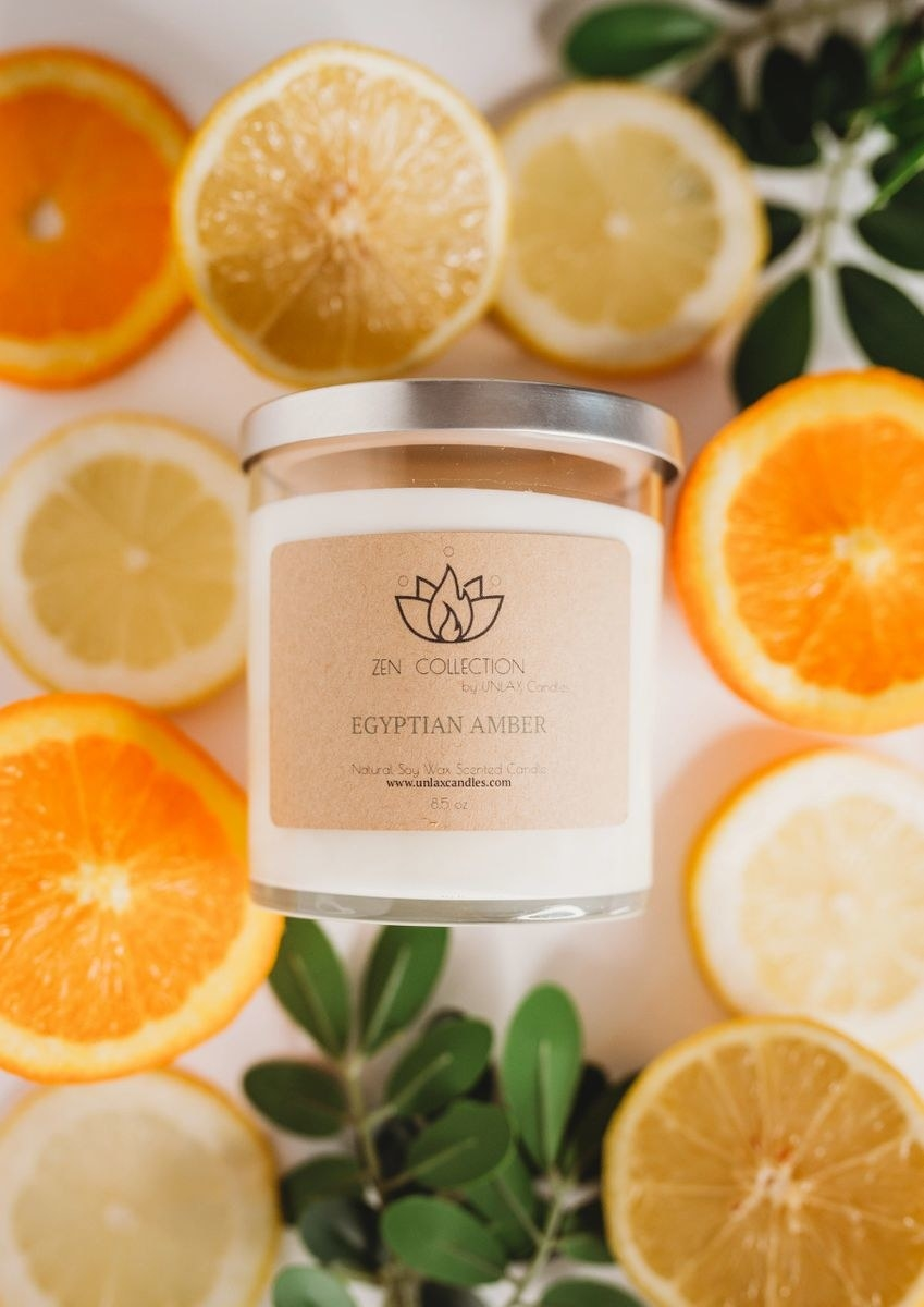 white candle with minimal label on a bed of orange slices