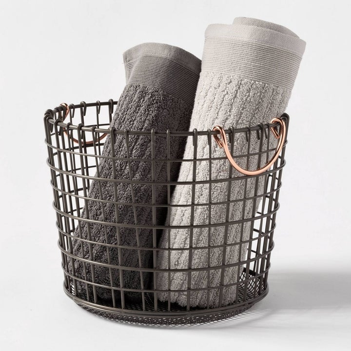 A round wire basket with two copper handles holding towels