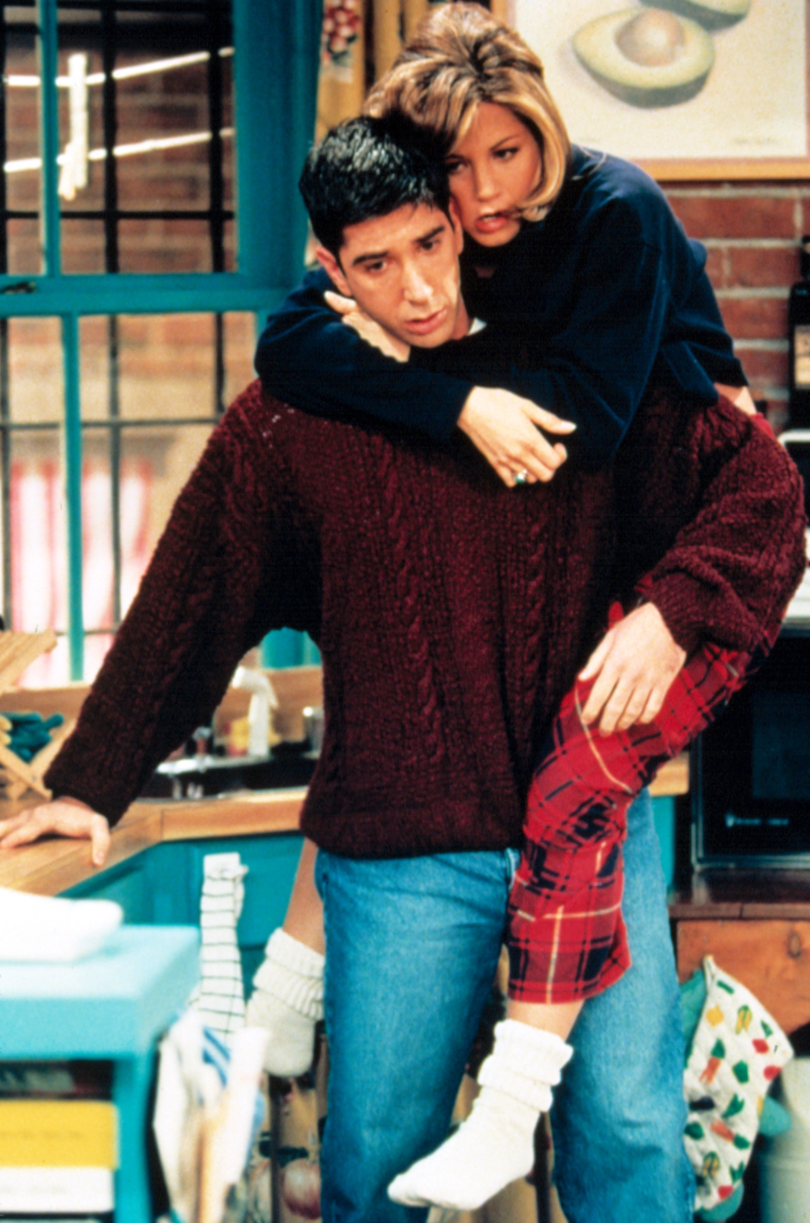 Rachel on Ross's back trying to stop him from listening to a voicemail on Friends