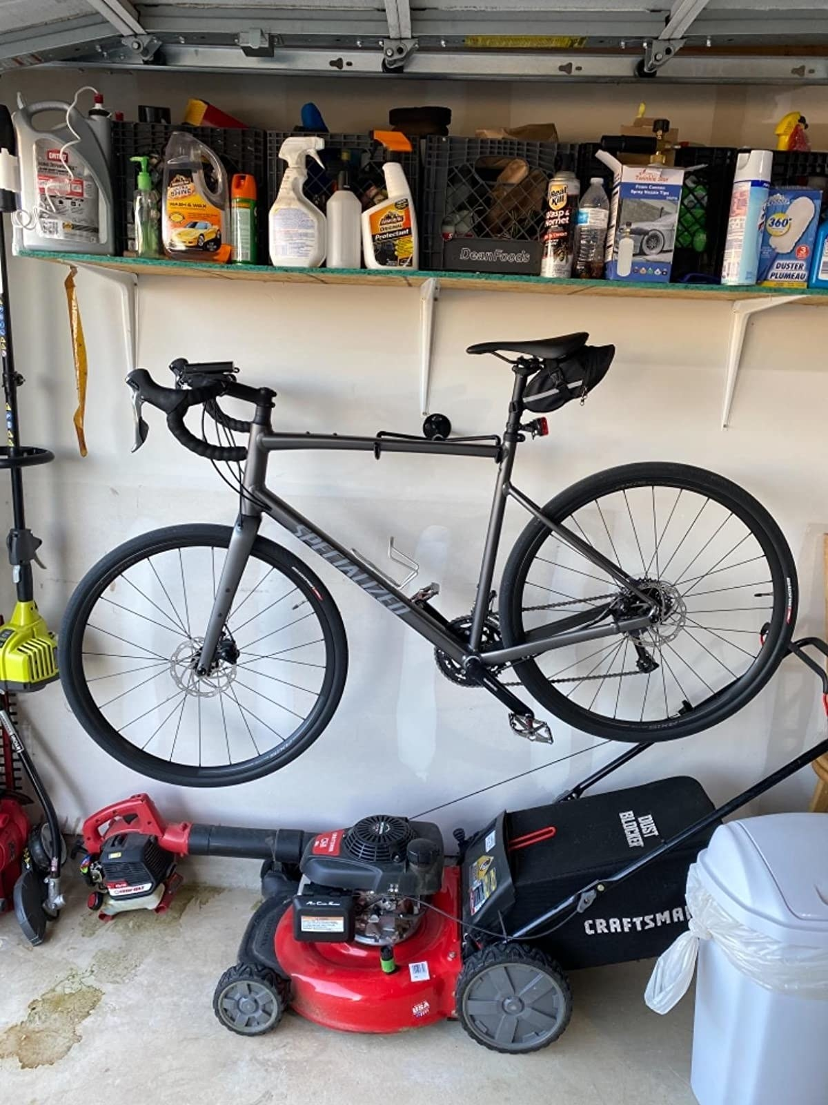 A reviewer's photo of their bike hanging from the mount in their garage