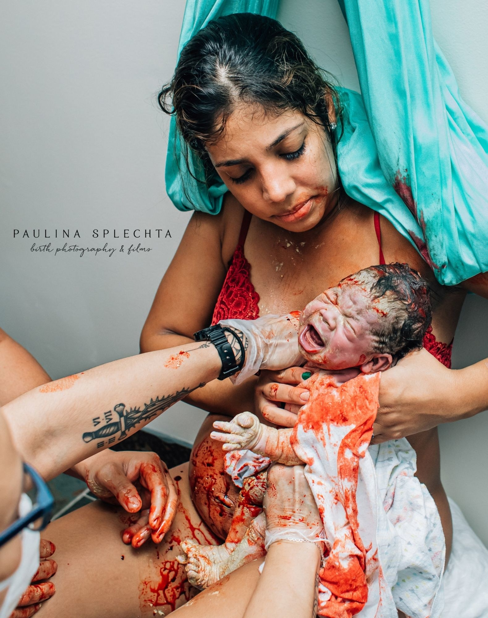 A bloody newborn is cleaned off as their mother holds them