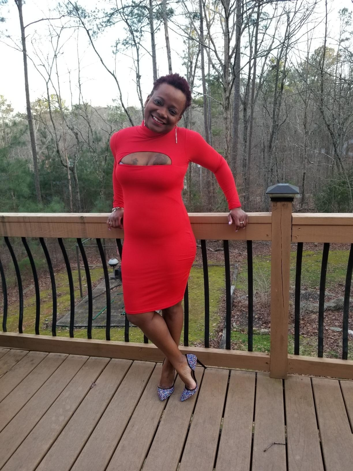 reviewer wearing the knee-length dress in bright red