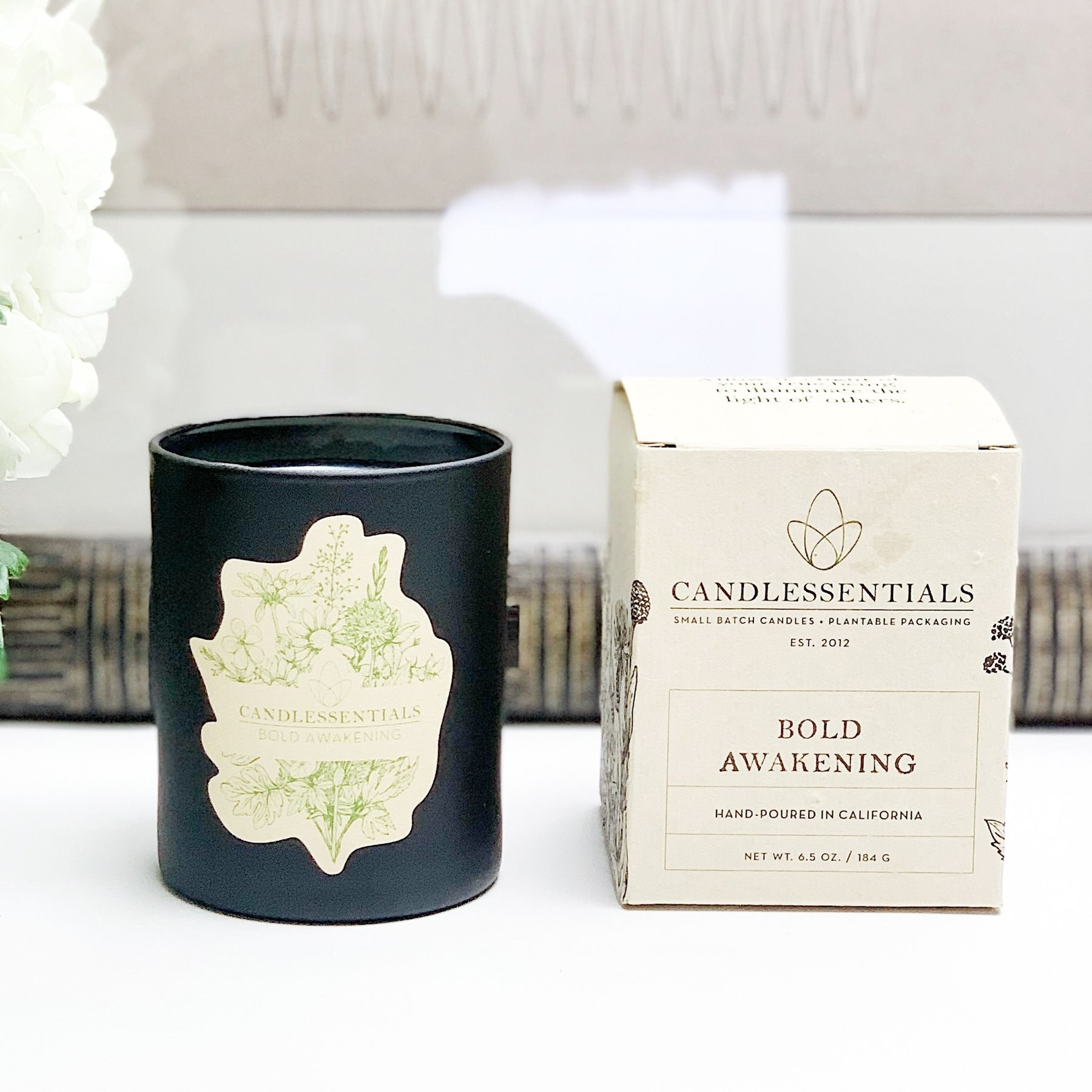 candle in a black jar with a botanical label and the candle box beside of it