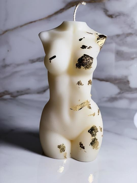 white female form torso candle with bits of gold leaf on it