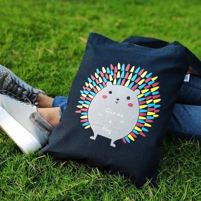 A dark blue tote bag with a hedgehog print