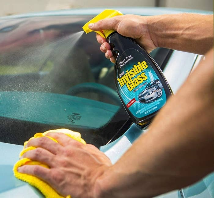 A model spaying the glass cleaner onto a car and wiping it with a microfiber cloth