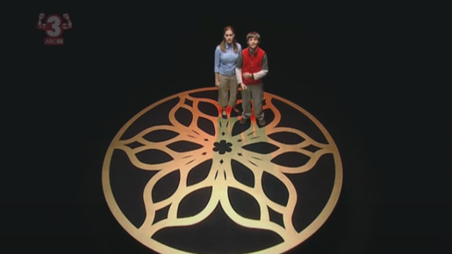 Ben and Veronica standing on top of a gold symbol in a black room