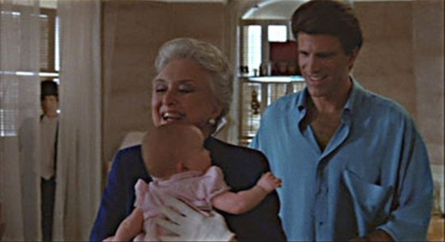 A screen shot from Three Men a Baby which features the Ted Danson cutout in the window