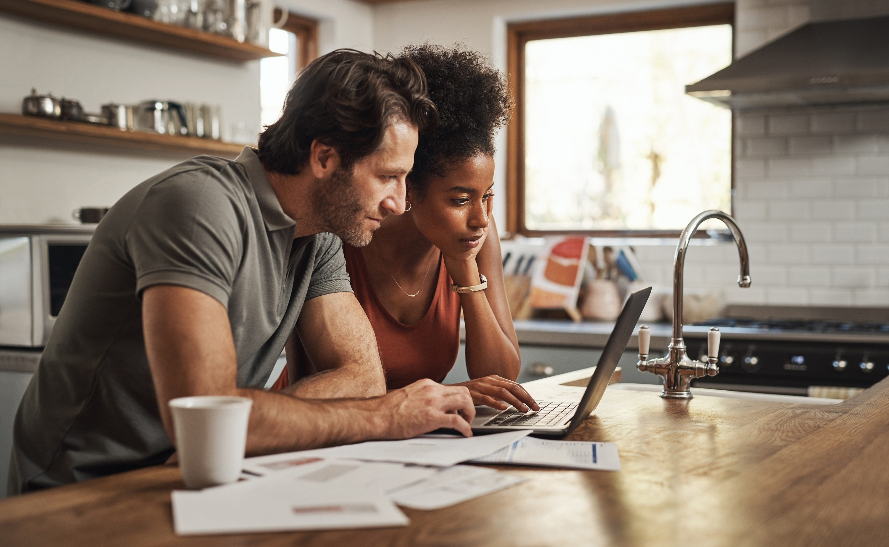 Couple looking at paperwork and laptop together