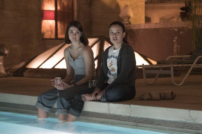 Callie and Mariana sitting by a pool at night and drinking