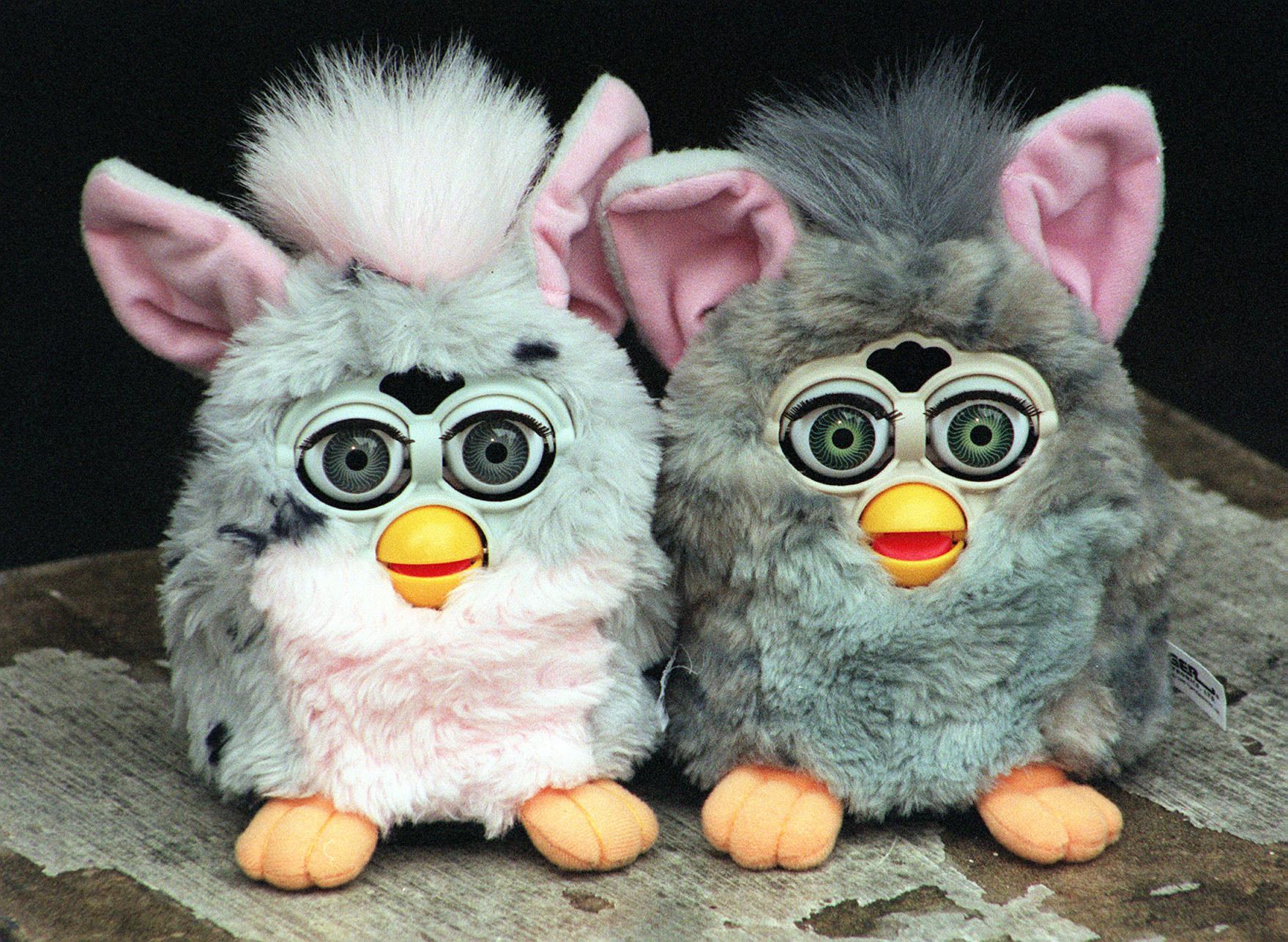 Two grey Furbies set on worn table