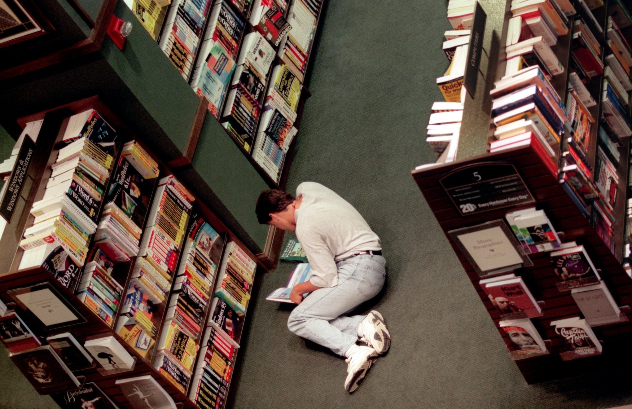 Overhead photo of a man on the floor of a Barnes & Noble reading books