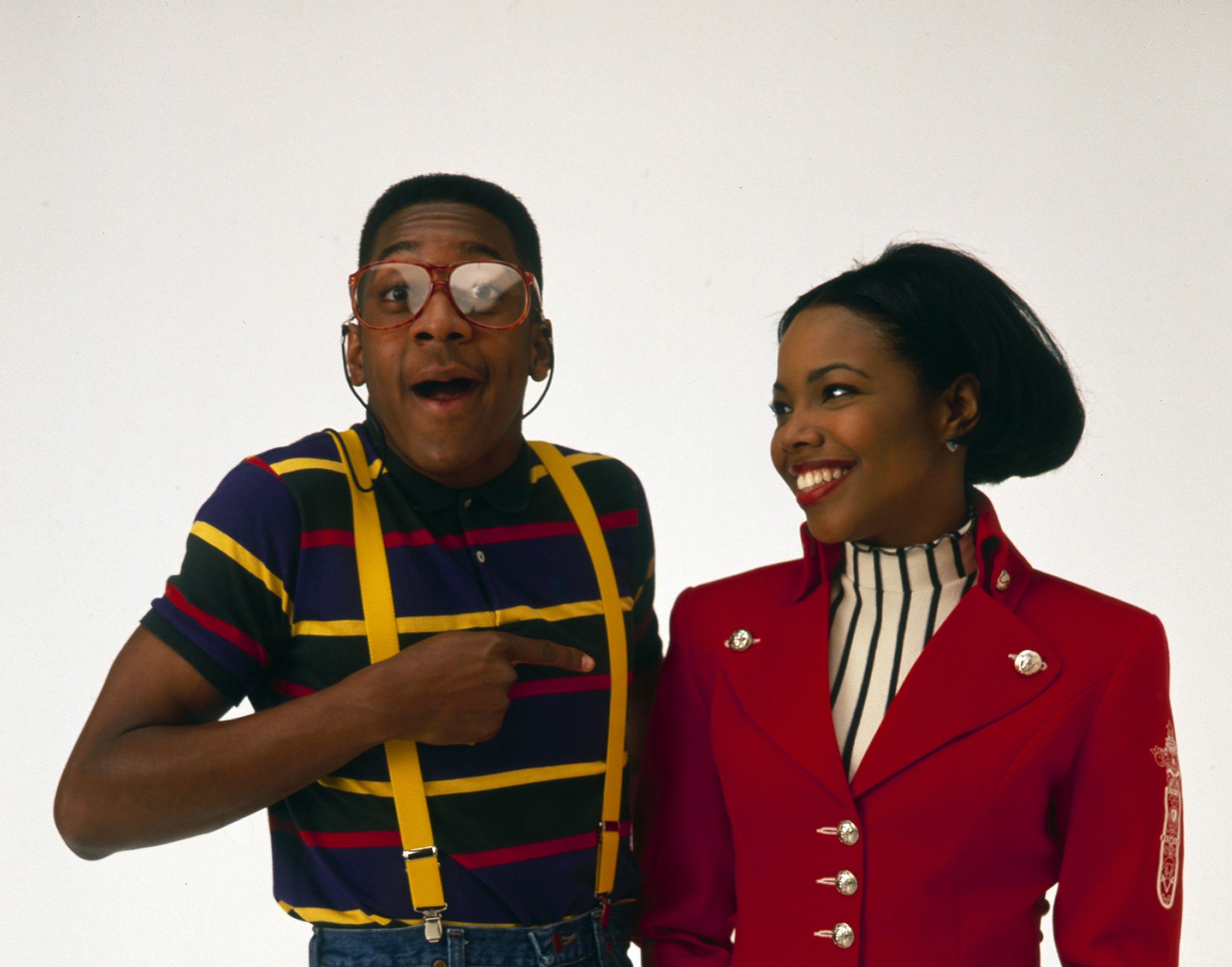 Photo of Urkel in a striped polo and yellow suspenders pointing to Laura wearing a red blazer