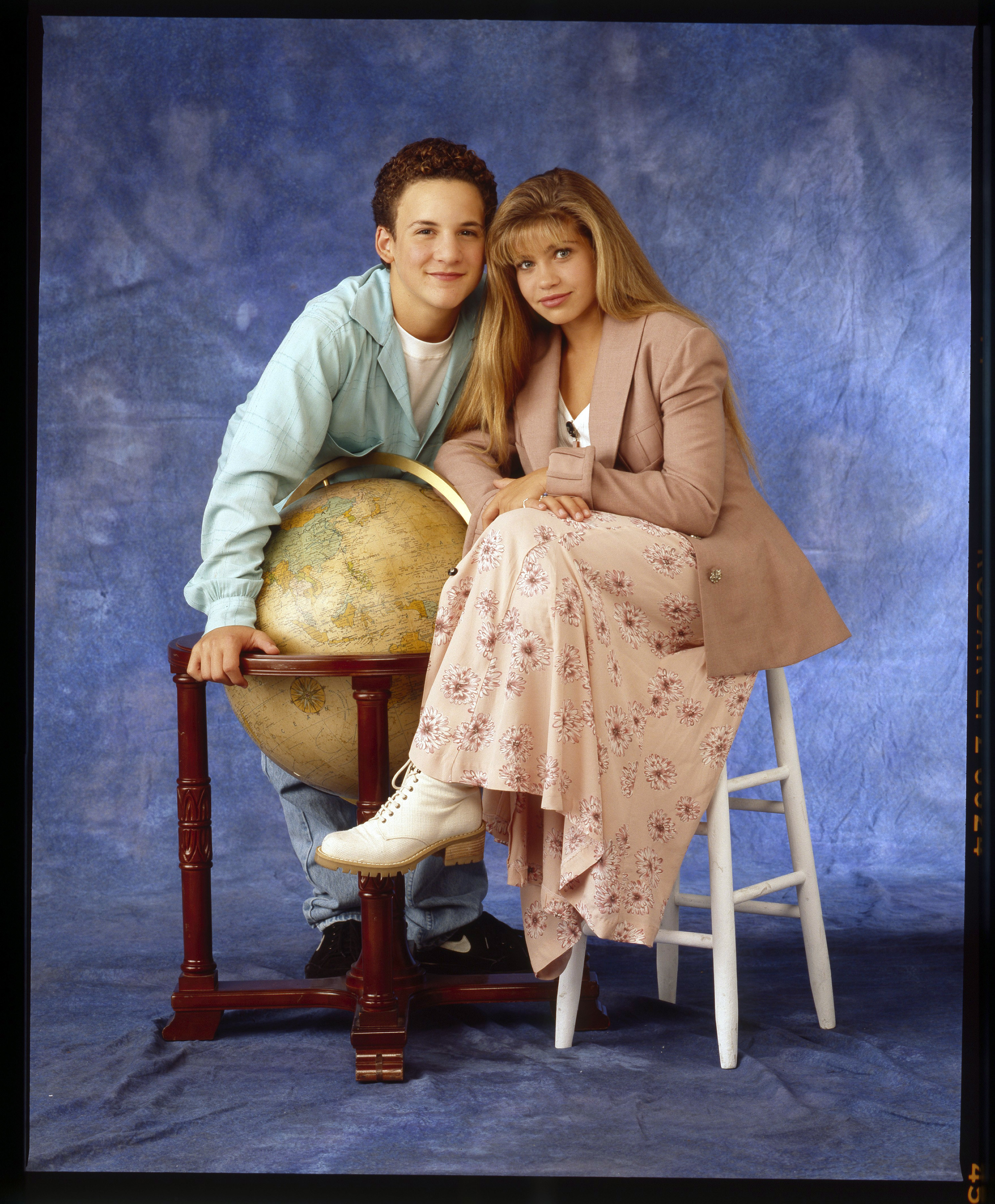 A photo of Cory and Topanga leaning on a globe with a tie-dye blue background