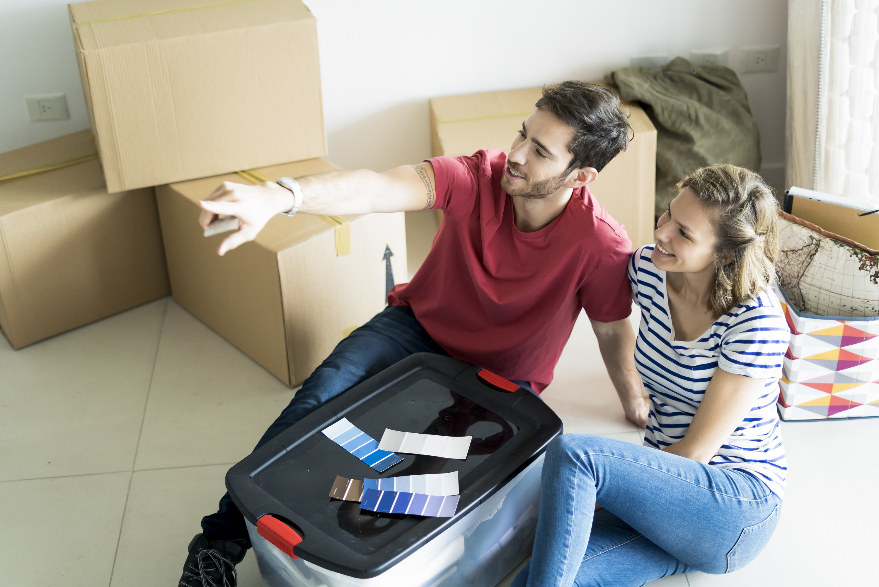 Couple sitting on the floor of their new home surrounded with boxes