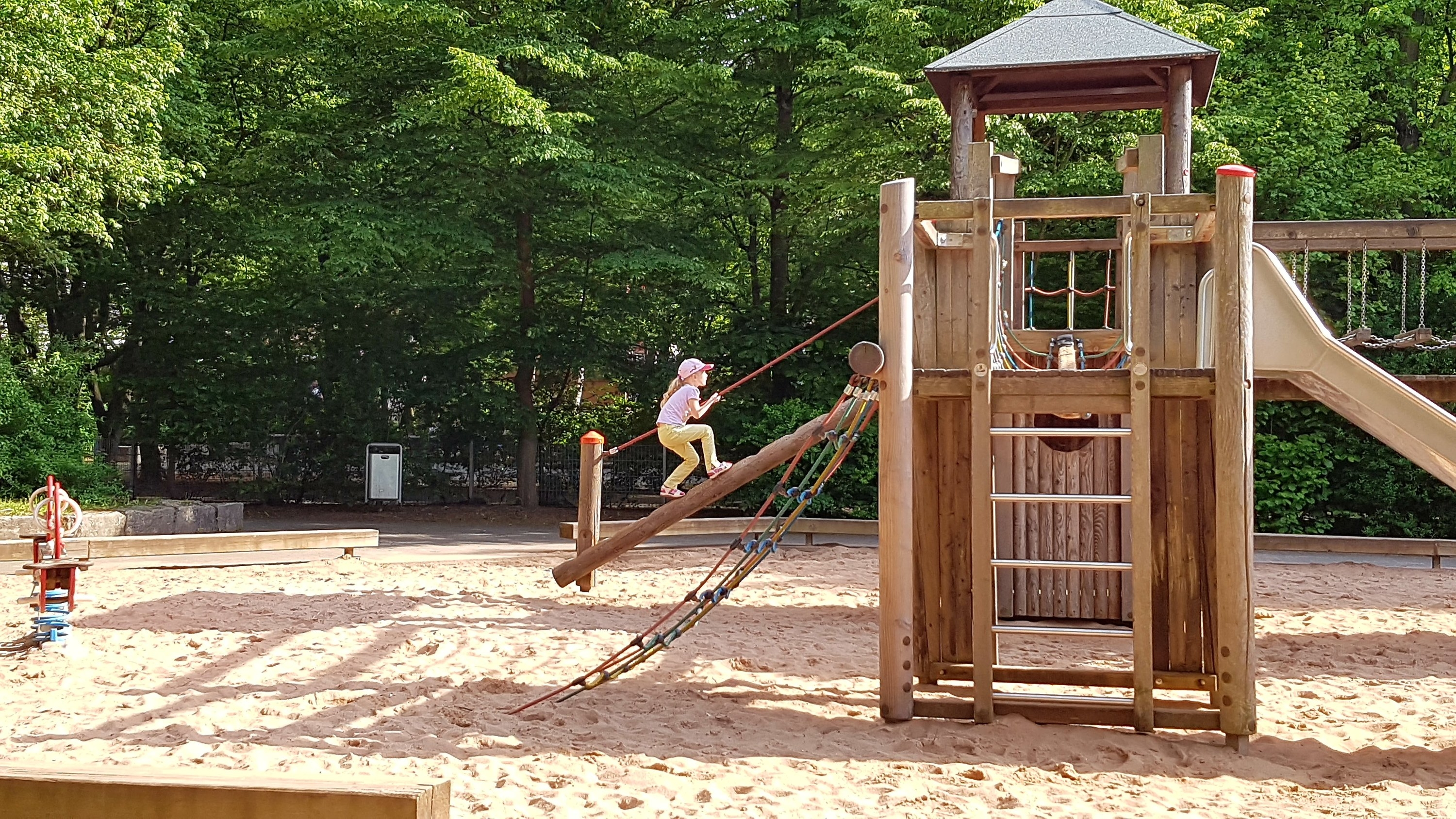 Photo of a girl climbing up the rope log of a wooden playground
