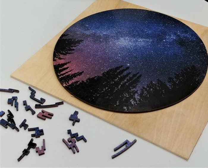 a circle puzzle of black forest trees and a starry night sky
