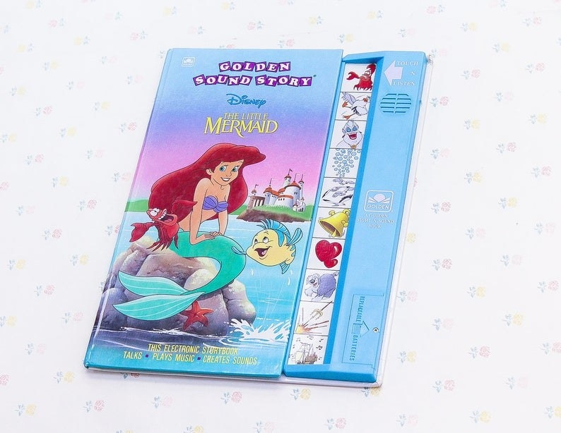 The Little Mermaid sitting on a rock with Sebastian and Flounder on the cover of the book