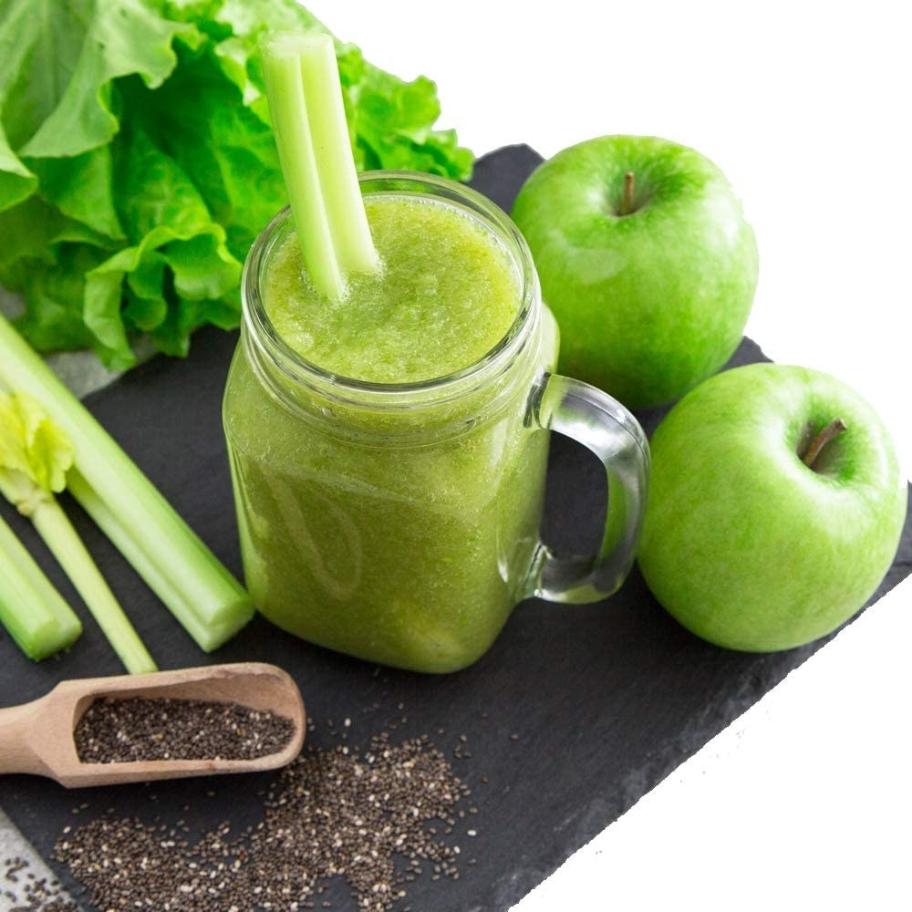 mason jar of celery juice surrounded by apples and celery