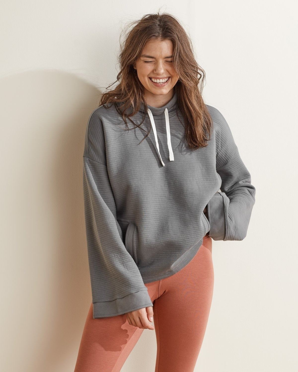 model wearing the gray hoodie with the white drawstring