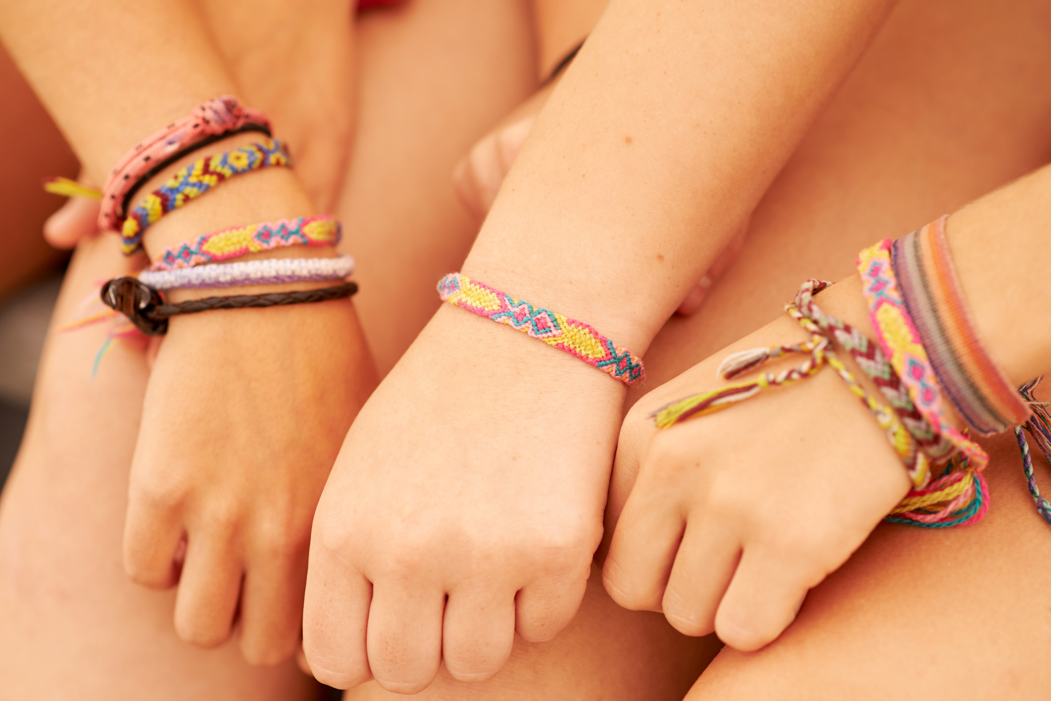 Three kids showing off their friendship bracelets