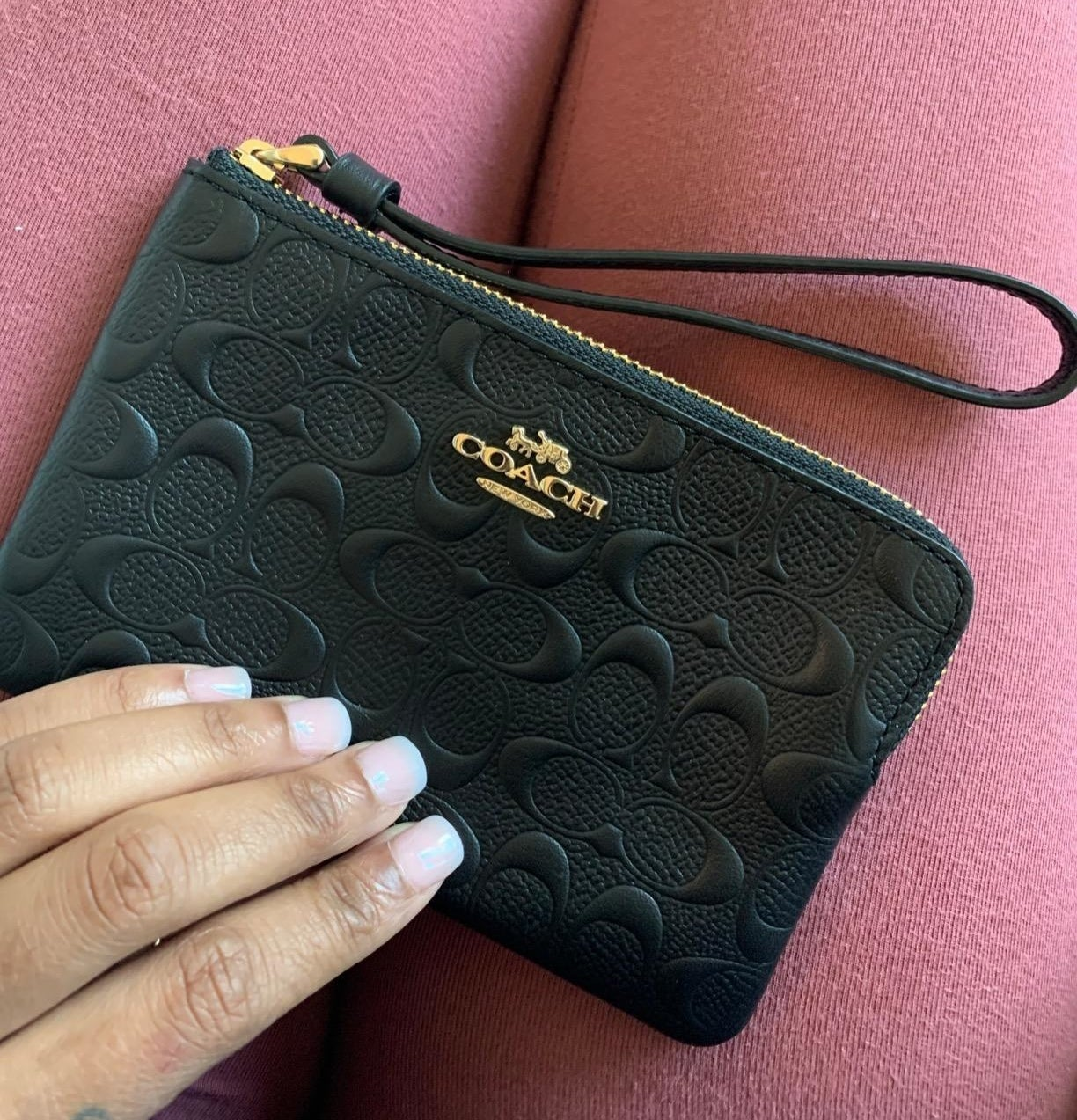 a reviewer's photo of the black wristlet which has gold Coach branding