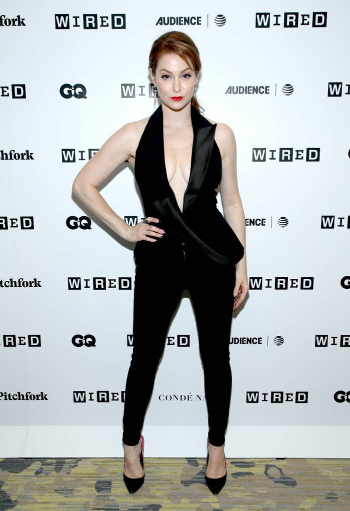 Esme Bianco wearing a v-cut tuxedo top with matching skinny pants and heels on the red carpet at the WIRED Cafe at Comic Con event in 2018