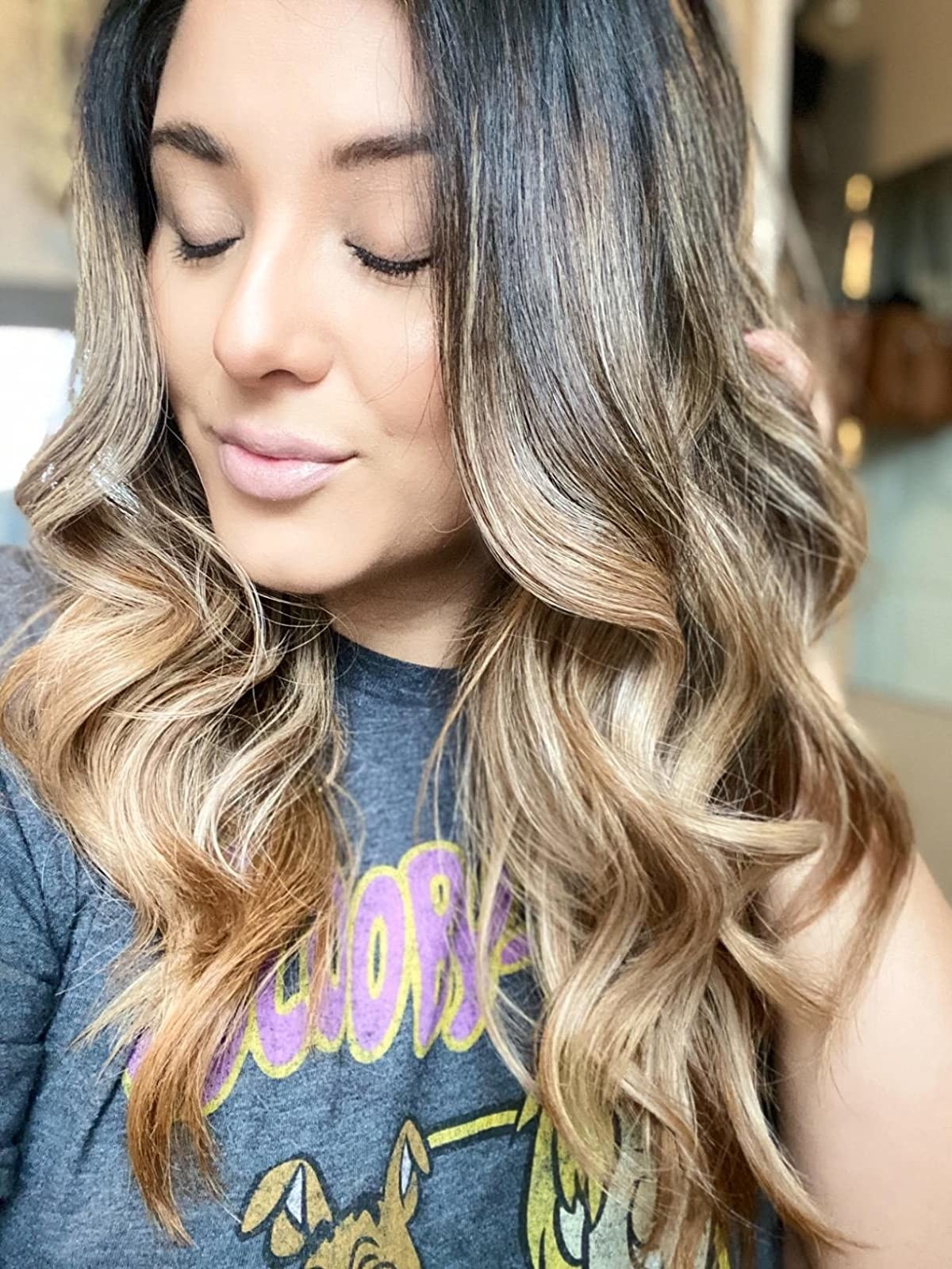 Reviewer showing off her curls achieved by using the wand
