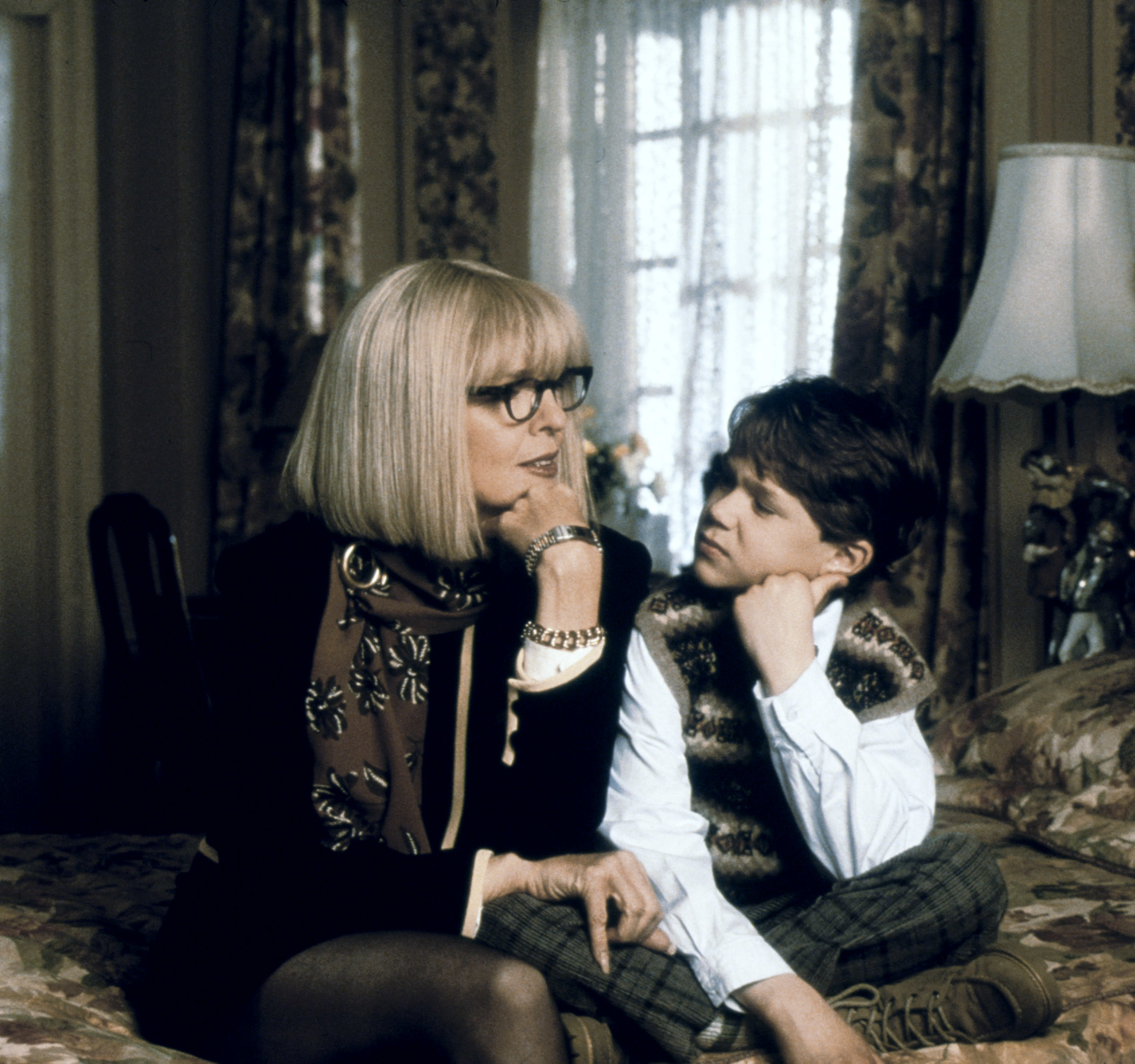 Diane Keaton in a blonde bob cut sitting on a bed next to a little boy looking at her