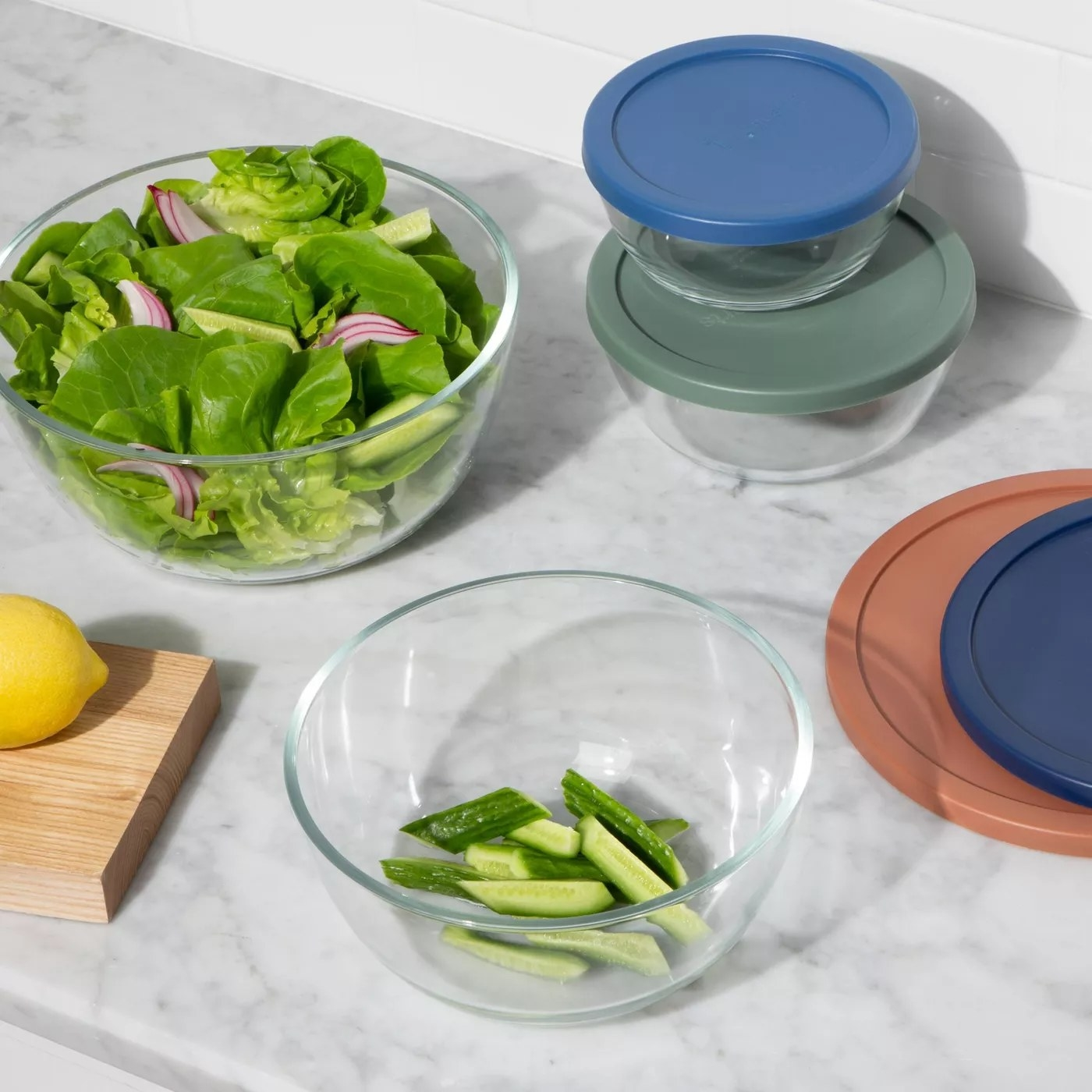 the glass bowls on a counter with veggies inside