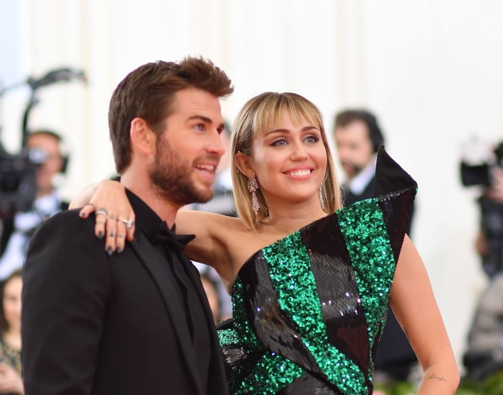 Miley Cyrus, wearing a two-toned sequined dress, and Liam Hemsworth, in a monochrome tux, pose together at the 2019 Met Gala