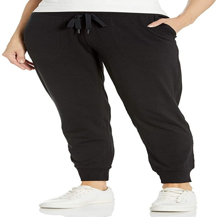 Model wears black joggers with white sneakers